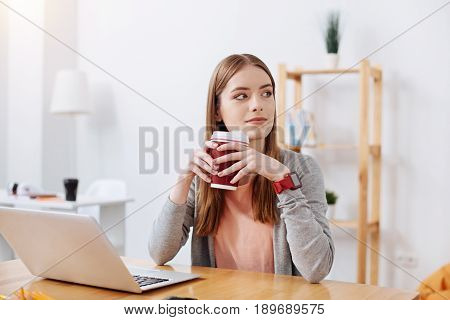 Rest for energy. Productive dedicated young woman enjoying a cup of coffee while getting ready for working on her assignment