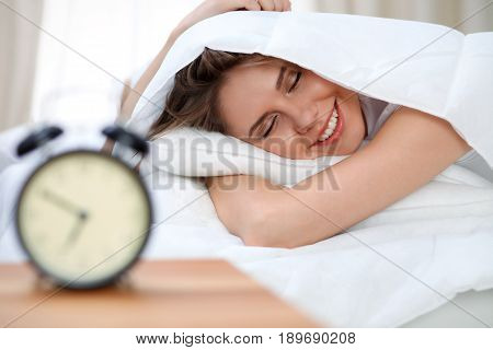 Sleepy young brunette woman smiling befor waking up with alarm ringing.