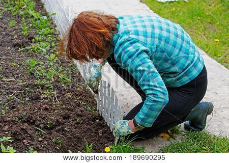 Woman Fixing A Decorative Fence On A Flower Bed