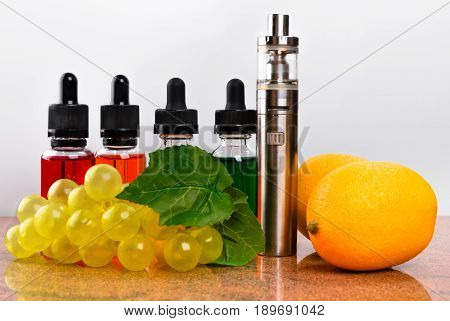 Electronic cigarette bottles with vape liquid lemons and fake bunch of grapes on granite surface and white background