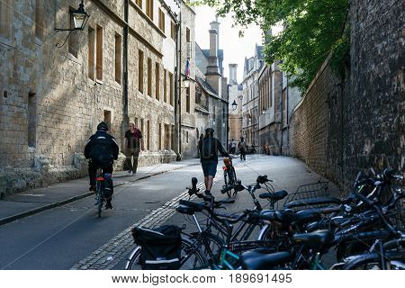 OXFORD, UNITED KINGDOM  - MAY 22, 2017: Cyclists and people walking down the street of Oxford, city famous for it's prestigious university established in the 12th century.