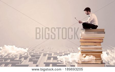 A businessman with laptop tablet in elegant suit sitting on a stack of books on top of sandy labirynth background concept