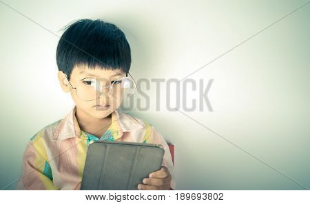 Nerdy Genius boy is using Tablet with copy space