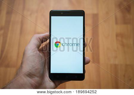 London, United Kingdom, june 5, 2017: Man holding smartphone with Google chrome logo on the screen. Laminate wood background.