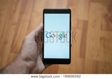 London, United Kingdom, june 5, 2017: Man holding smartphone with Google logo on the screen. Laminate wood background.