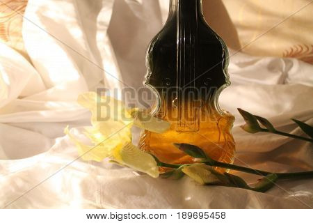 crystal bottle with wine in shape of violin and yellow iris in bloom beautiful decoration