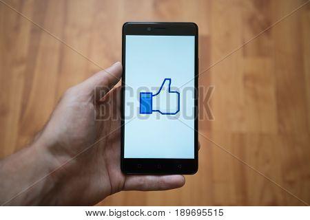 London, United Kingdom, june 5, 2017: Man holding smartphone with Facebook like thumb logo on the screen. Laminate wood background.