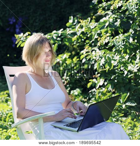 Woman working on a laptop outdoors in summer garden