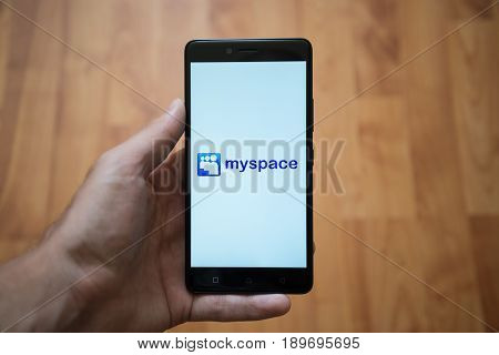 London, United Kingdom, june 5, 2017: Man holding smartphone with Myspace logo on the screen. Laminate wood background.