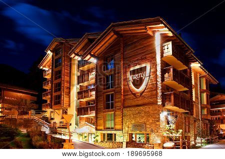ZERMATT SWITZERLAND OCT 20 2010: Night view on chalet in Swiss cottage style - hotel Firefly. Classic Swiss chalet architecture. Matterhorn peak. Swiss holidays vacations tourists travel tours