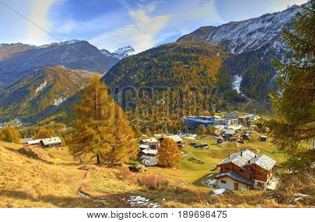 View on hotels chalets in Swiss cottage style and Alpine mountains in summer. Swiss chalets cottages in Alpine mountains. Matterhorn peak. Swiss holidays tours