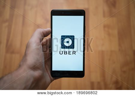 London, United Kingdom, june 5, 2017: Man holding smartphone with Uber LOGO on the screen. Laminate wood background.