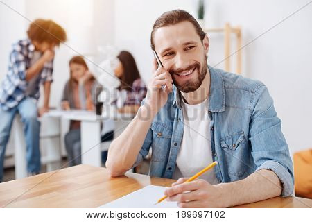 Do you have a moment. Handsome delighted vibrant man sitting in the classroom and looking pleased while chatting with his fellow student