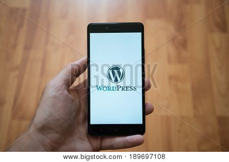 London, United Kingdom, june 5, 2017: Man holding smartphone with Wordpress LOGO on the screen. Laminate wood background.