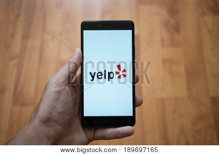 London, United Kingdom, june 5, 2017: Man holding smartphone with Yelp LOGO on the screen. Laminate wood background.