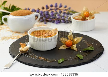 Creme brulee with Physalis and brown sugar. Creme brulee dessert with lavender and coffee on black shale