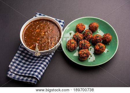 Gobi Manchurian dry or with gravy - Popular street food of India made of cauliflower florets, selective focus