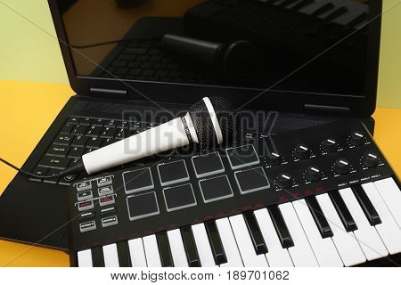 Musical instrument - MIDI keyboard laptop and vokal microphone for a karaoke on a flavovirent background.