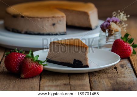 Homemade chocolate cheesecake on rustic wood table. Baked chocolate cheesecake. Triangle slice piece of cheesecake. Delicious chocolate cheesecake for relaxing time. Cheesecake chocolate on white plate.