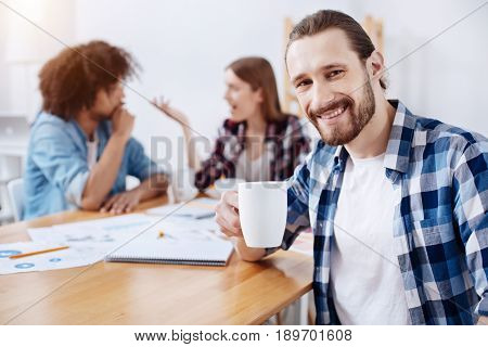 Great people, great company. Nice relaxed sociable man sitting at the table and holding a cup with hot drink while his colleagues discussing something in the background