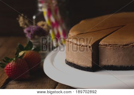 Homemade chocolate cheesecake on rustic wood table. Baked chocolate cheesecake. Triangle slice piece of cheesecake. Delicious chocolate cheesecake for relaxing time. Piece of chocolate cheesecake.