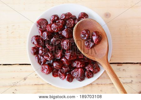 Dried cherries on a white plate with a wooden spoon