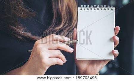 Closeup image of a woman holding and showing blank notebook in office