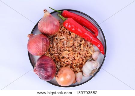 Dried shrimp, fresh Bombay onions, fresh red chilies, fresh shallots, fresh garlics on a white ceramic plate with blue outer ring line.  White background.