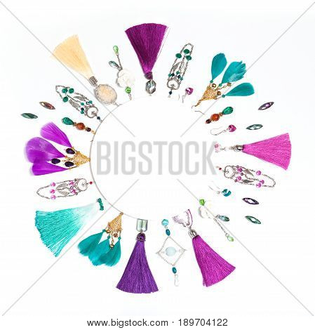 Handmade turquoise and violet bijouterie circle garland with earrings, necklace, gems, tassels, feathers in boho style, lying flat on the white square background, top view, with round empty place for text