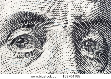 Benjamin Franklin's eyes on a hundred-dollar bill close-up