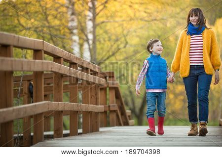 Portrait of happy mother with cute smiling son walking in a wooden bridge countryside. Woman with kid boy in the park. Together. Lifestyle