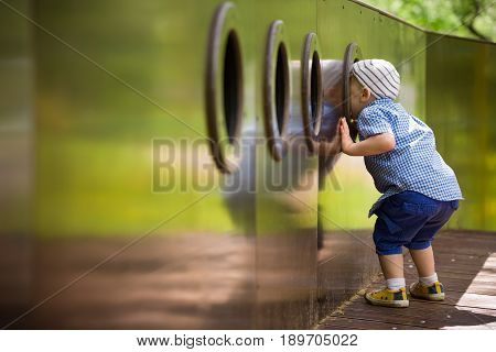 Toddler boy looking out of the window on wooden playground. Child playing on outdoor ship on a sunny summer day.