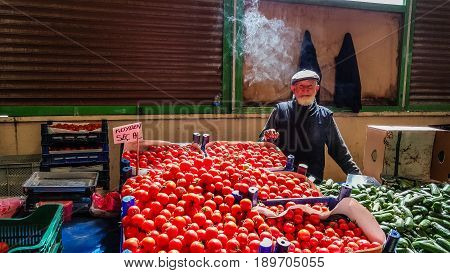 Eskisehir, Turkey - May 25, 2017: Elderly Man With Smoke Upon His Head Selling Tomatoes And Cucumber