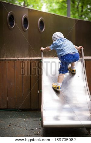 Toddler boy climbing up on metal slide of the playground. Child playing on outdoor wooden facilities on a sunny summer day.