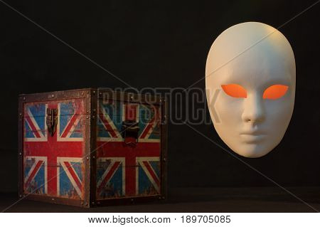 Concept of terrorism.England flag box and mask on dark background