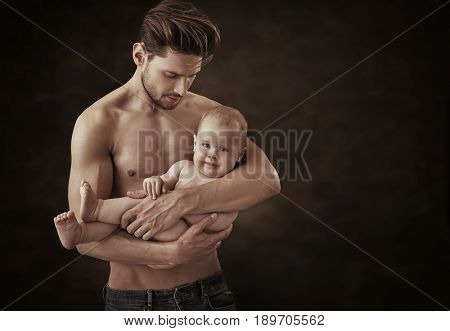 Muscular father holding his little baby