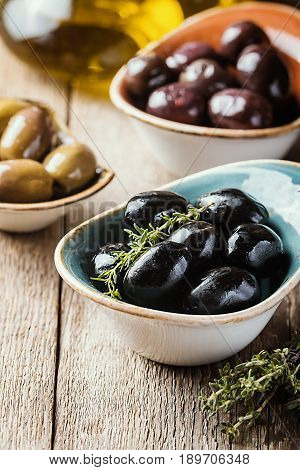 bowls with different kind of olives green olives, black olives, kalamata olives with olive oil