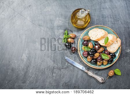 Olive oil, different olive fruites and fresh bread. Top view Testing fresh mediterranean extra virgin olive oil.