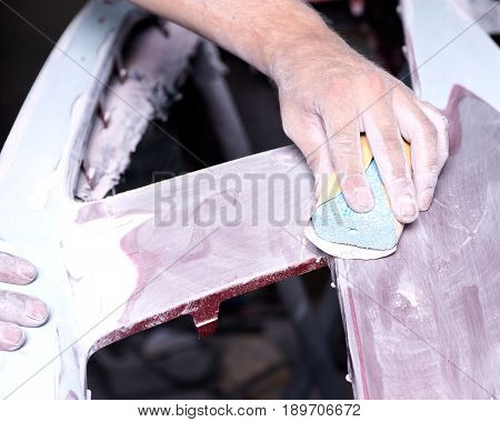 Worker is sanding filler in auto body shop