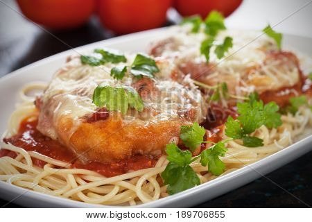 Breaded parmesan chicken with melted cheese and tomato sauce served over spaghetti pasta