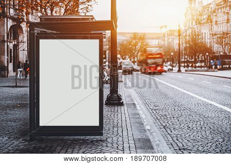 White empty information mock-up on city bus stop blank vertical billboard near paved road with red touristic bus clear placeholder frame in urban settings with copy space for text or advertising