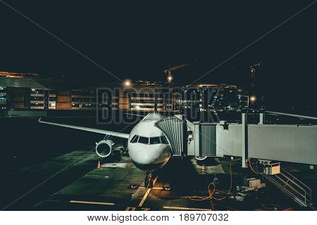 Aircraft maintenance at night airport front view of handling passenger airplane parked jet plane with retractable gangway in Domodedovo airport of Moscow through the gate window in darkness