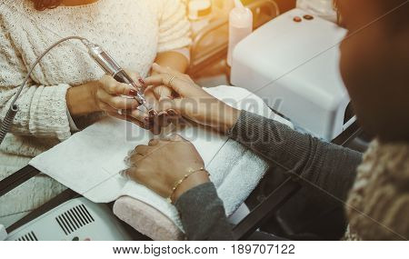 Close-up view of hands of afro american brown woman in nail salon receiving manicure master preparing nails for shellac manicure using special rotating nail file machine device