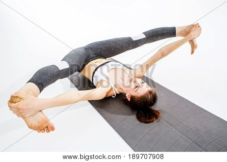Woman doing twine lying on rug at blank background