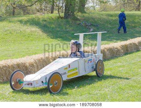 STOCKHOLM SWEDEN - MAY 21 2017: Happy girl driving a home made soapbox car downhill on a field in the race Gardesloppet at Djurgarden Stockholm Sweden. May 21 2017