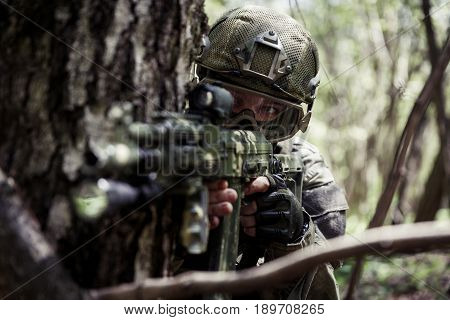 Photo of sighted soldier with submachine gun in woods