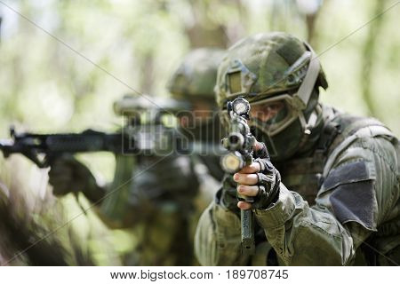 Portrait of officers with weapons on reconnaissance in forest