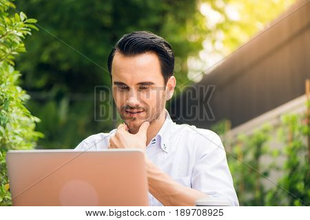 Satisfied businessman working on laptop with internet wireless
