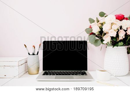 Home office desk with blank screen laptop beautiful roses and eucalyptus bouquet white vintage casket in front of pale pastel pink background. Blog website or social media concept .