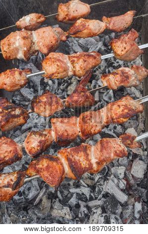 Pieces of tasty pork on skewers cooking on smoldering carbons outdoors